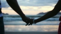 couple-holding-hands-at-sunset-silhouetted